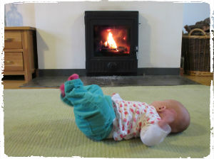 The PFS baby enjoys the warmth from our wood burning stove in Sycamore Cottage